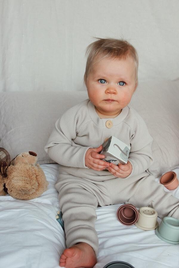 Lapsi pitää lelupalikkaa kädessä ja istuu peitolla, Ajaton Paita ja Seikkailu Housut Pellavan sävyssä