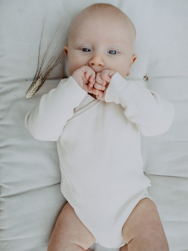 Vauva makaa Vaniljan sävyinen Halaus Body yllään
