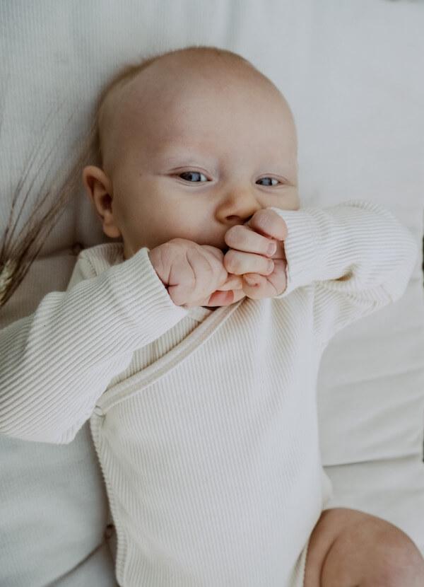 Vauva makaa pitäen käsiä suun edessä, Halaus Body yllään