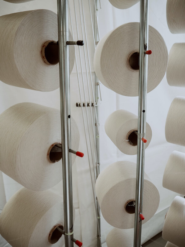 Valkoista lankaa, josta valmistuu kangasta tehtaassa