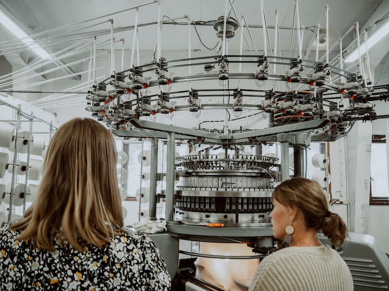 Naiset katsovat kuinka tehdaskone valmistaa kangasta tehtaassa