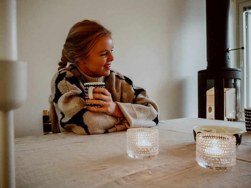 Nainen istuu tuolilla ja hymyilee teekuppi kädessä