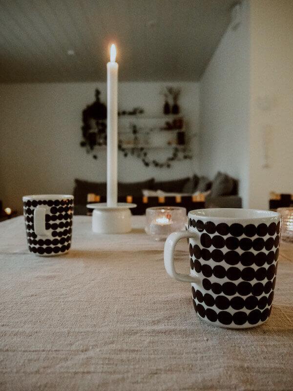 Teekupit pöydällä, kynttilässä tuli