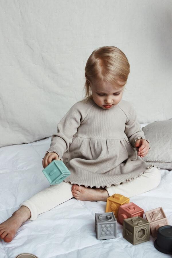 Tyttö leikkimässä palikoilla Pellavan sävyinen Lempi Mekko ja Vaniljan sävyiset Runo housut päällä