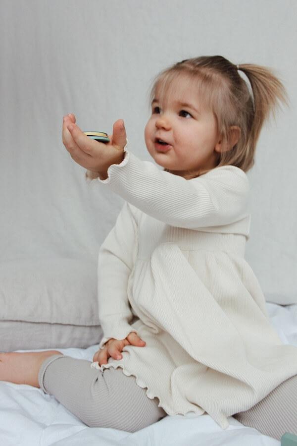 Pikkutyttö ojentaa lelua Lempi Mekko päällä