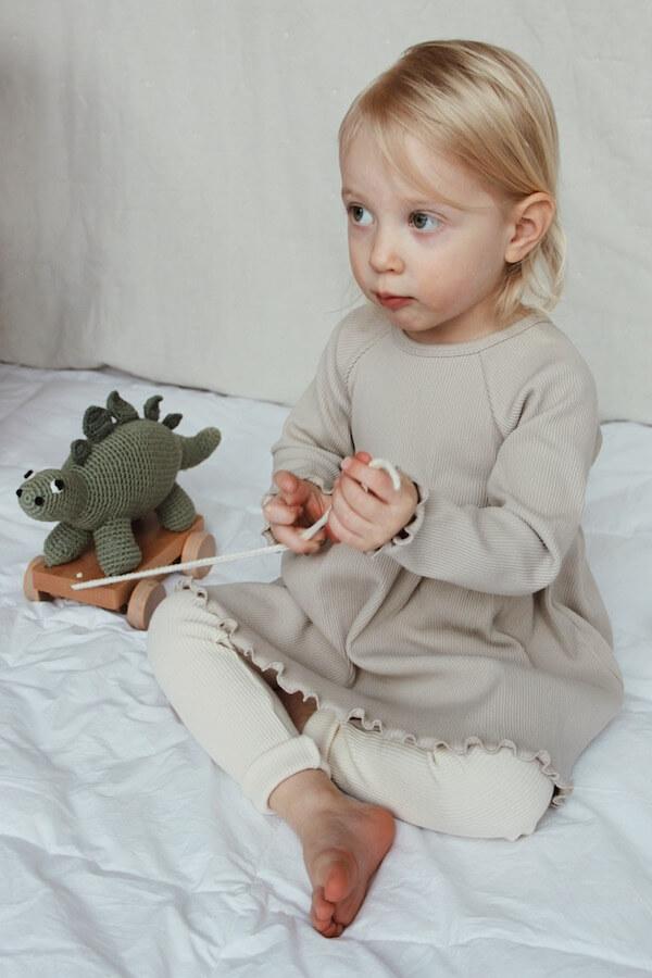 Tyttö istuu peitolla lelun kanssa yllään ihana Lempi Mekko ja Runo Housut