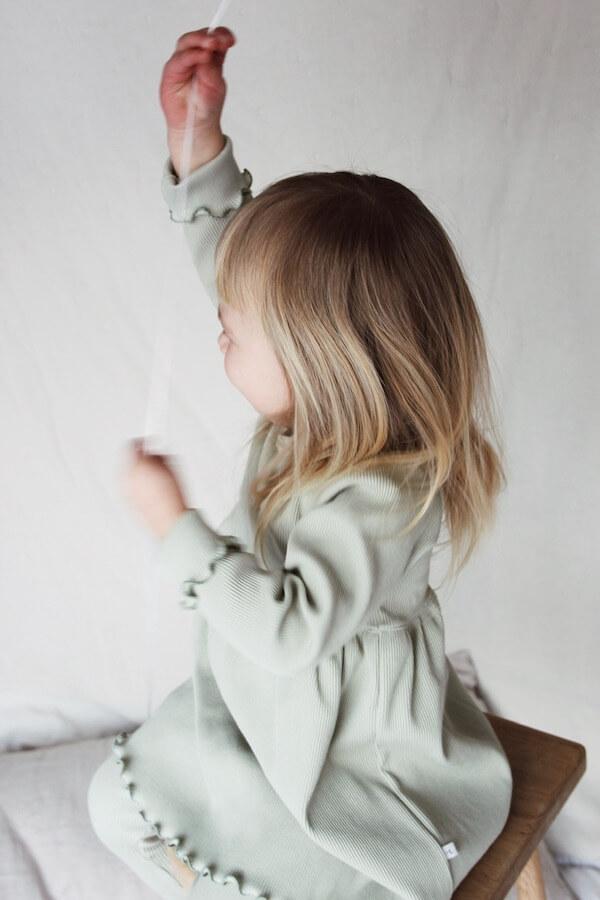 Tyttö heiluttaa käsiään, kuvattu sivusta