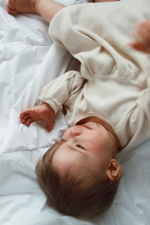 Tyttö makaa peitolla Lempi Mekko päällä