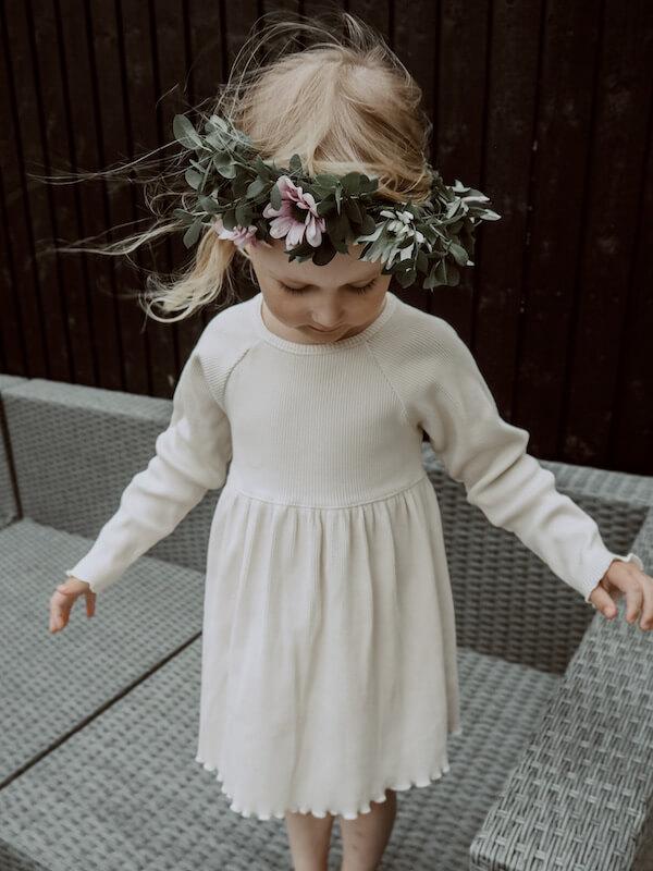 Tyttö seisoo terassisohvalla Lempi Mekko yllään ja Kukkaseppele päässä