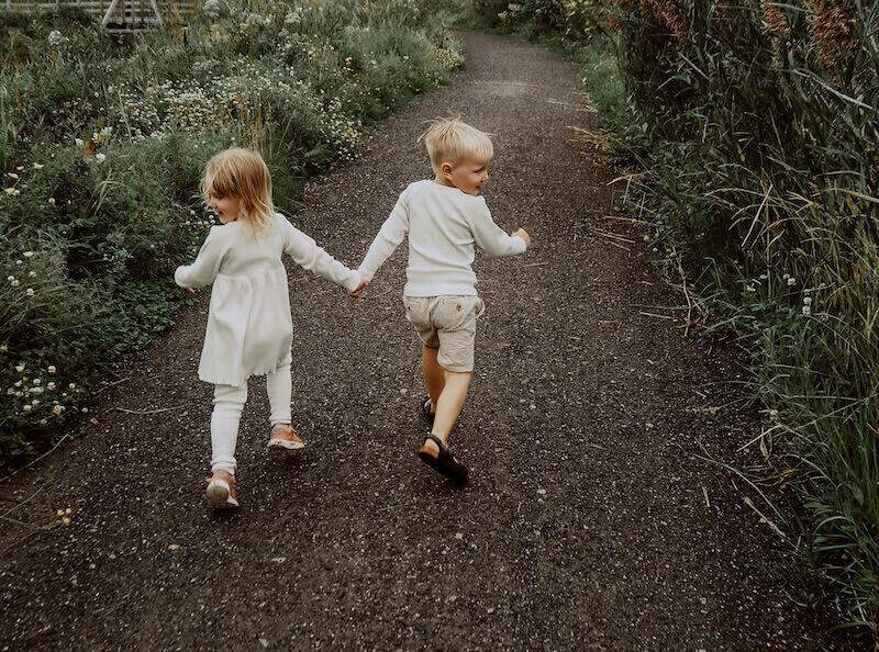 Tyttö ja poika juoksevat, yllään Vaniljan sävyinen Lempi-mekko, Runo-housut ja Ajaton-paita
