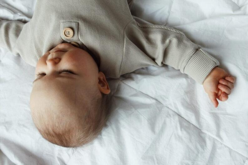 Lapsi kuvassa ylösalaisin, makaa peitolla