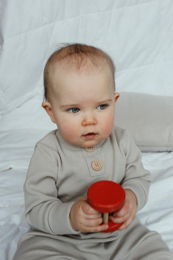 Lapsi istuu Rento Haalari päällä peitolla, kädessä lelu