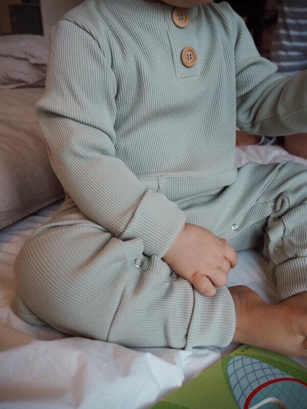 Sumunvihreä Rento Haalari istuvan lapsen päällä
