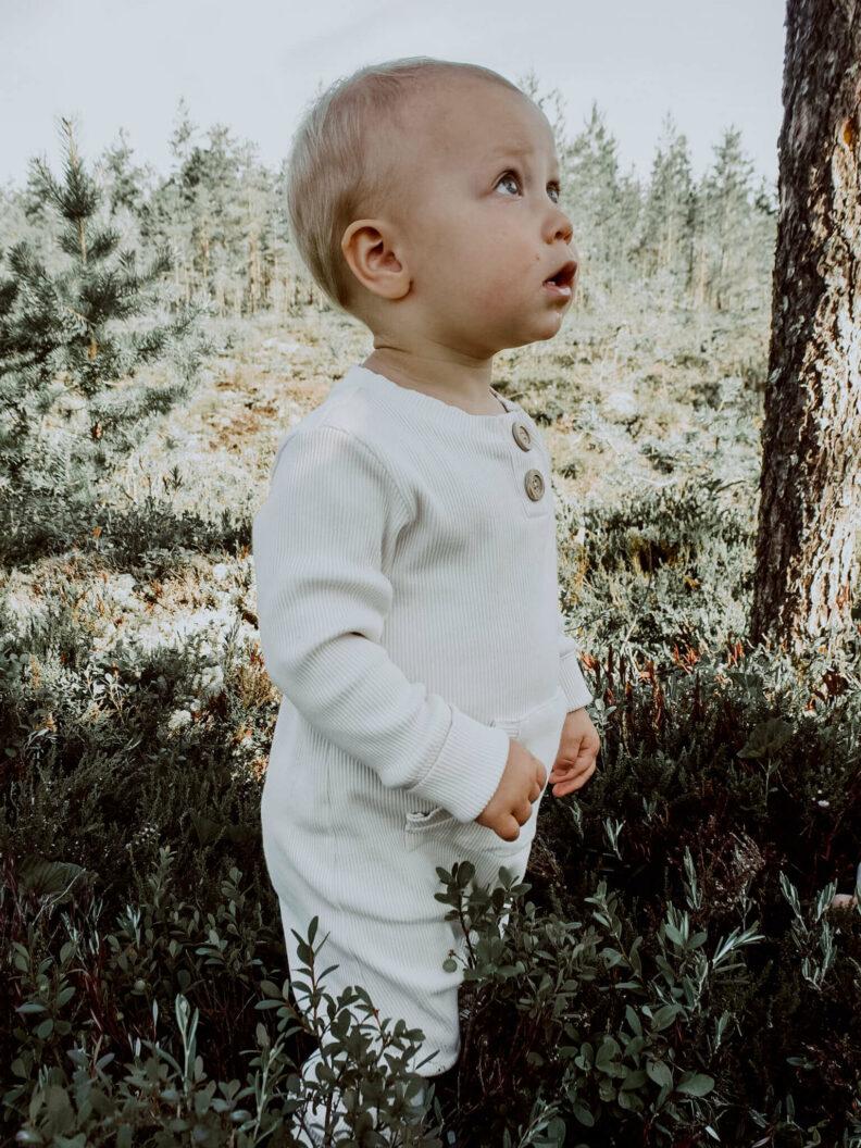 Lapsi seisomassa suolla Vaniljan sävyinen Rento Haalari yllään