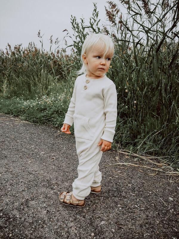Lapsi katsoo taaksepäin, yllään Vaniljan sävyinen Rento Haalari