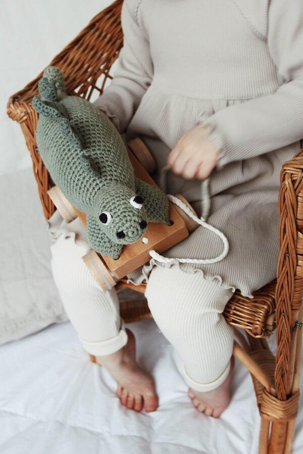 Lähikuvassa lapsi jolla dinosaurus lelu sylissä