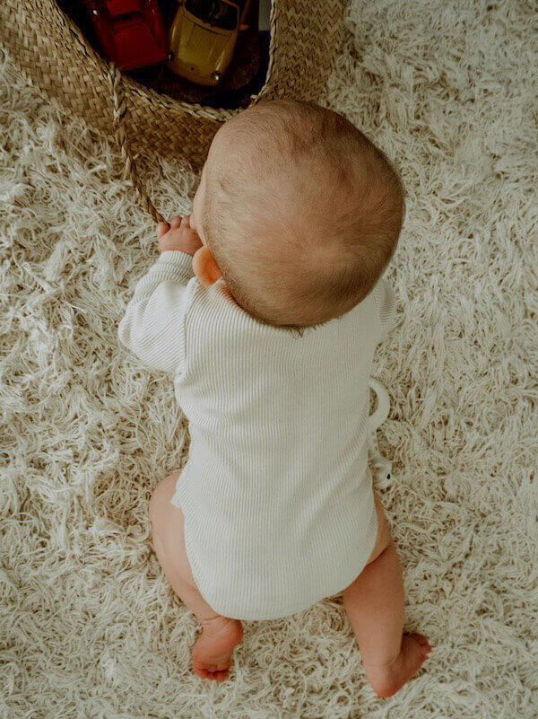 Vaniljan sävyinen Uskallus Body vauvan päällä