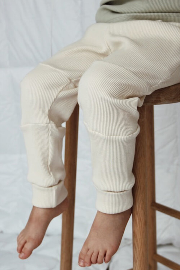 Lapsi istuu tuolilla jalassaan Seikkailu Housut Vaniljan sävyssä