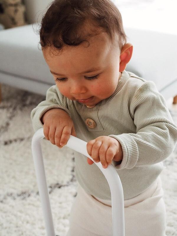 Vauva työntää kärryä yllään Uskallus Body ja Runo Housut