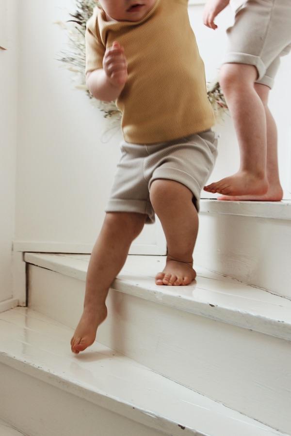 Lapset laskeutuvat portaita yllään Aito Paita ja Aarre Shortsit