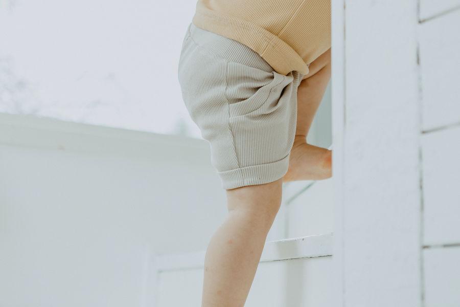 Lähikuvassa portaita kiipeävä lapsi Pellavan sävyisissä Aarre Shortseissa