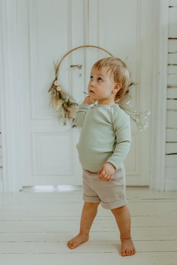 Poika leikkii harsokukalla huoneessa, taustalla kaunis kuivakukkakranssi