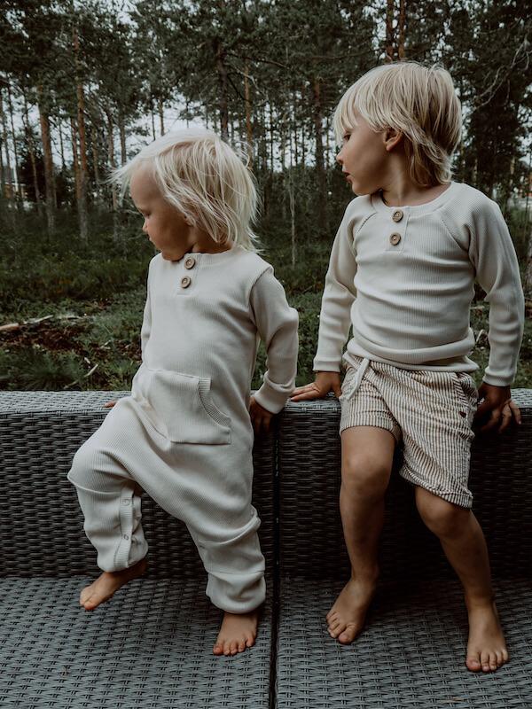lapset istuvat ulkosohvalla, yllään ihanat Vaniljan sävyiset vaatteet