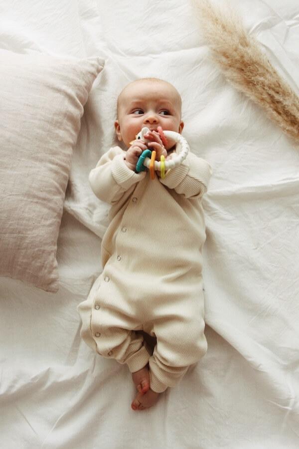 Vauva makoilee lakanalla lelu kädessään ja yllään Vaniljan sävyinen HENTO vauvahaalari