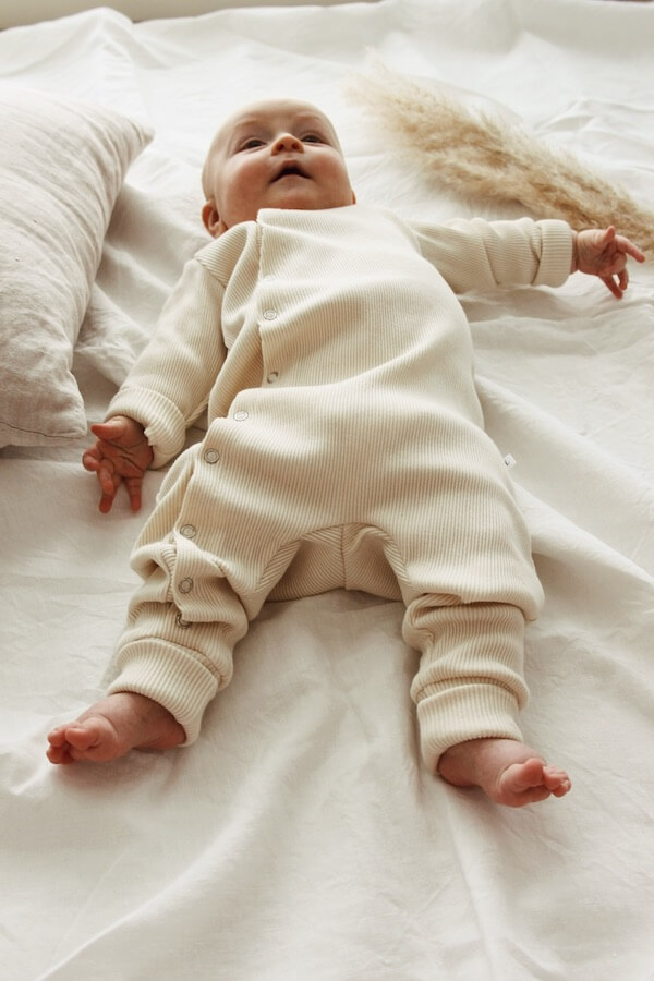 Vauva makaa valkean lakanan päällä Vaniljan sävyisessä HENTO vauvahaalarissaan