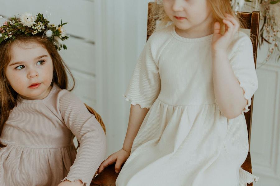 Tytöt istuvat tuolilla kukkaseppeleet hiuksissaan ja yllään Kielo ja Lempi Mekot
