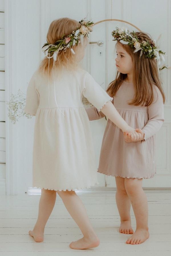 Tytöt tanssivat huoneessa yllään Kielo Mekko ja Lempi Mekko ja hiuksissaan kukkaseppeleet