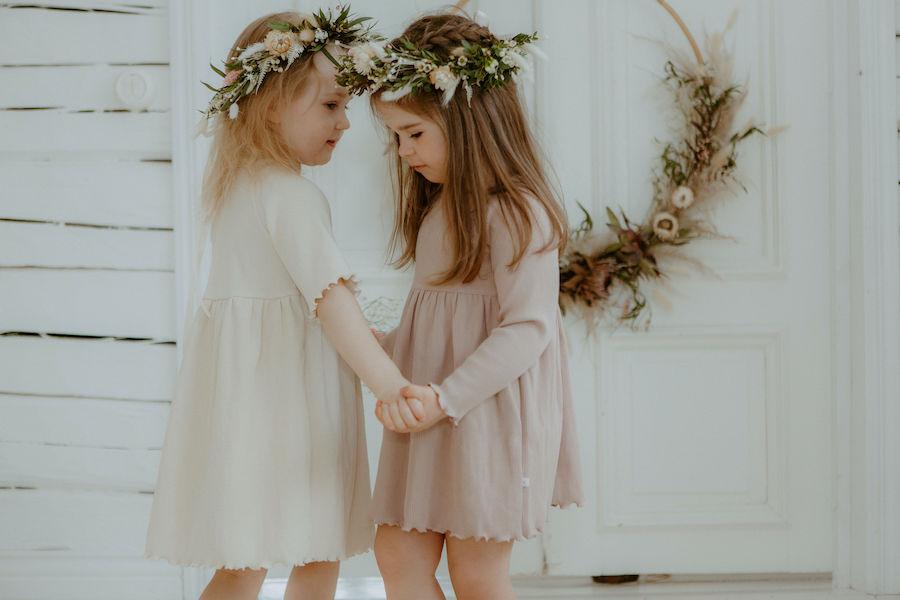 Tytöt tanssivat huoneessa Kielo ja Lempi Mekot päällä ja hiuksissa kukkaseppeleet