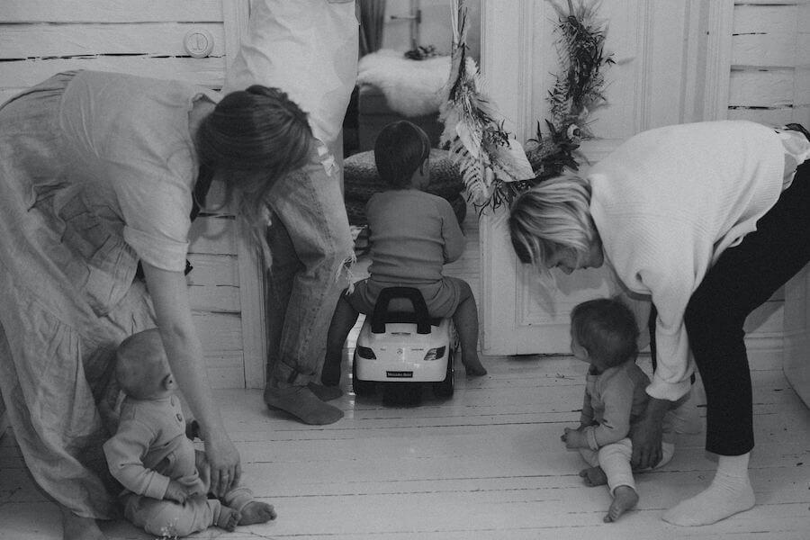 Aikuiset ja lapset leikkivät lattialla ihanassa kuvauspäivässä