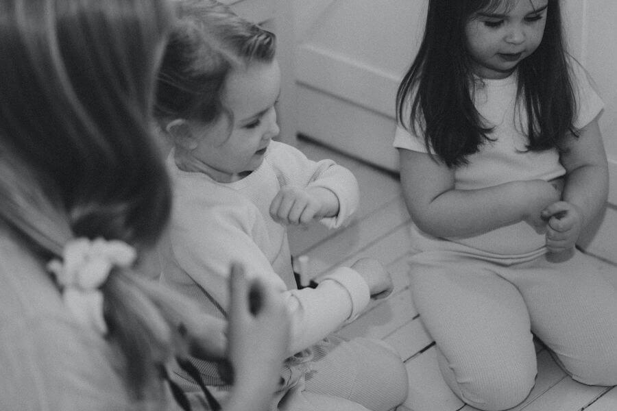 Nainen ja lapset laulavat ja leikkivät, lapsilla yllään ihanat ribbivaatteet