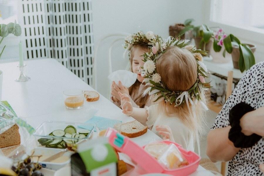 Tytöt syövät aamupalaa pöydän ääressä kukkaseppeleet päässään