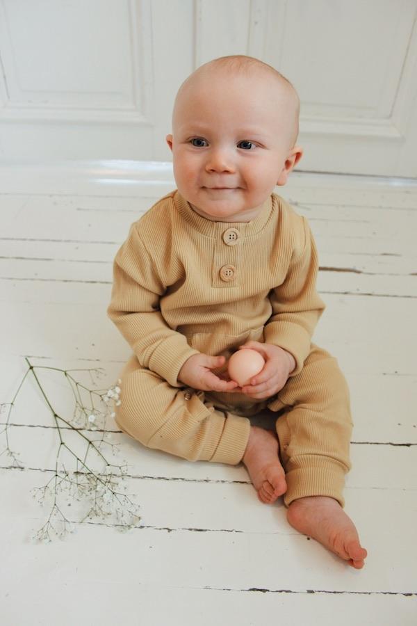Vauva istuu lattialla pallo kädessä ja yllään Oljen sävyinen Rento Haalari