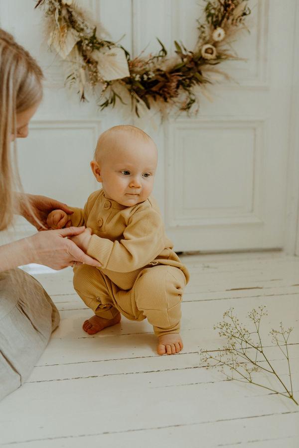 Vauva kyykistelee valkoisella puulattialla Oljen sävyisessä Rento haalarissaan, taustalla kukkakranssi
