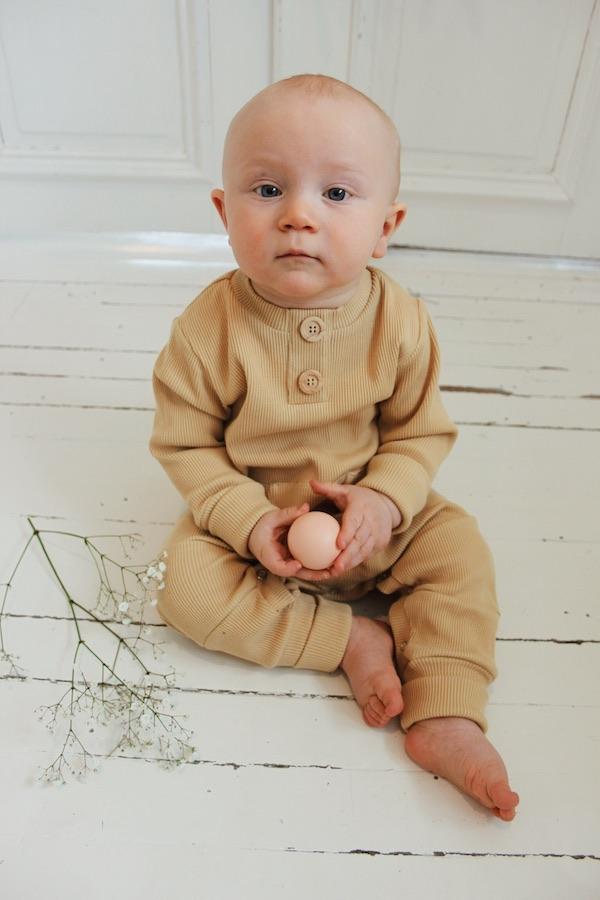 Vauva istuu ja ihmettelee lattialla Rento Haalarissaan