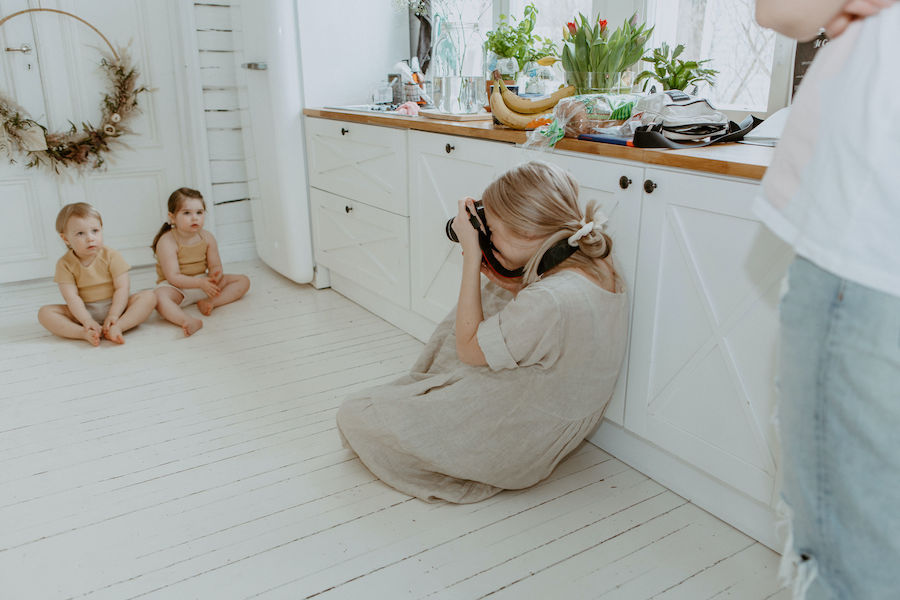 Nainen kuvaa lattialla istuvia lapsia kesäisissä ribbiasuissaan