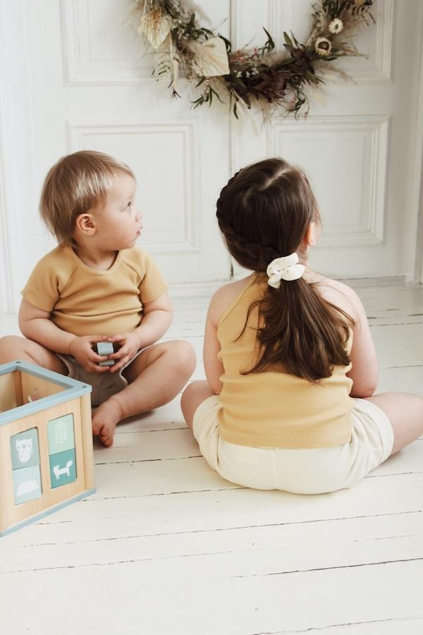 Tyttö ja poika istuvat puulattialla palikoilla leikkien