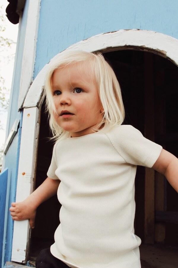 Vaniljan sävyinen AITO t-paita lapsen päällä liukumäessä