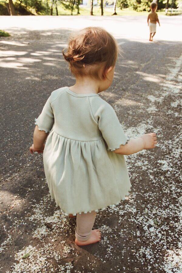 Tyttö kävelee puistotiellä yllään Sumunvihreän sävyinen KIELO mekko