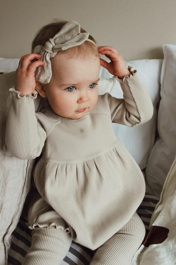 Tyttö istuu sängyn päällä, yllään ihana LEMPI mekko ja päässään rusetti