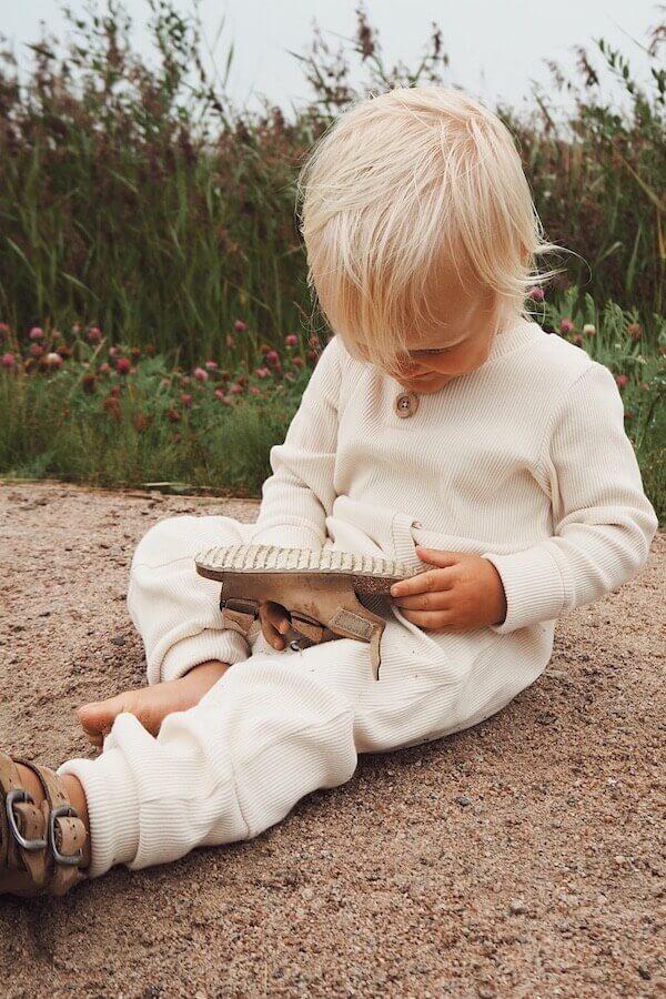 Lapsi istuu hiekkatiellä Vaniljan sävyisessä RENTO haalarissaan