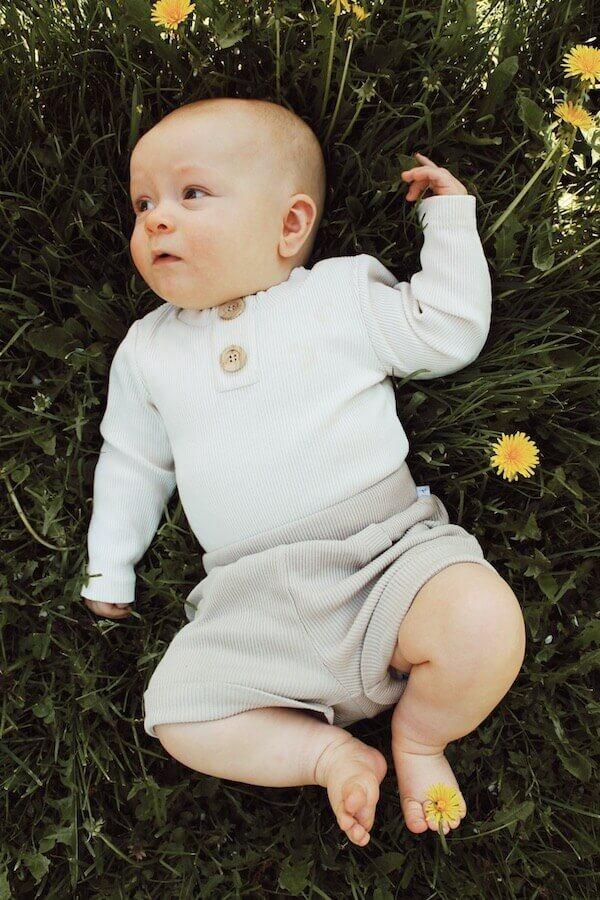 Vauva makaa kesänurmella ihanassa USKALLUS bodyssa sekä AARRE shortseissa